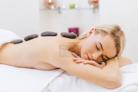 Photo pour Belle femme détendue obtenir la thérapie de pierre au salon de spa - image libre de droit