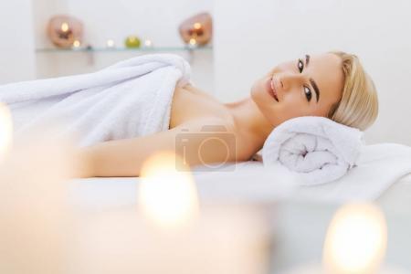 Photo pour Souriante jeune femme relaxante sur table de massage au salon spa - image libre de droit
