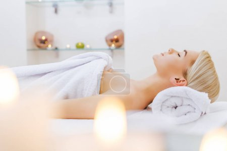 Photo for Attractive young woman relaxing on massage table at spa salon - Royalty Free Image