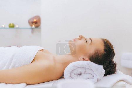 Photo pour Jeune femme relaxante sur table de massage au salon de spa - image libre de droit