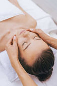 relaxed young woman getting facial massage at spa salon