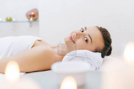 happy young woman relaxing on massage table at spa