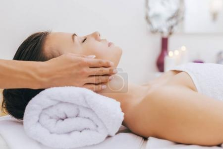 Photo for Close-up shot of young woman getting facial massage at spa salon - Royalty Free Image