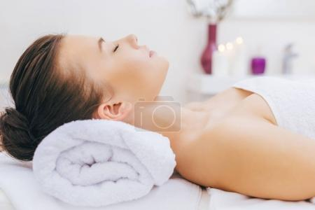 Photo for Beautiful young woman relaxing at spa with head on rolled towel - Royalty Free Image