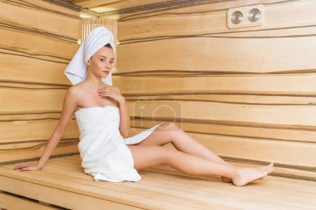 attractive young woman relaxing on bench at sauna
