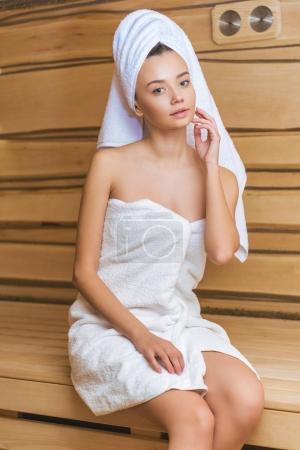 beautiful young woman in towels relaxing at sauna