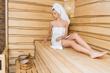 Photo pour Belle jeune femme relaxante sur banc au sauna - image libre de droit