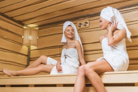 Photo pour Belles jeunes femmes assis sur un banc de sauna et de parler - image libre de droit