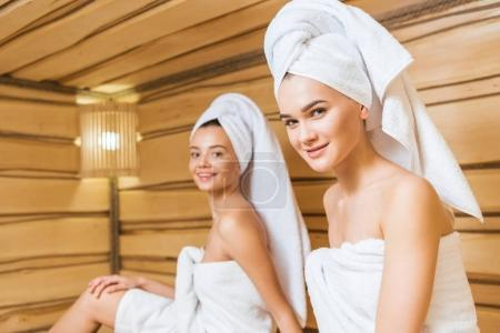 happy young women covered with towels relxing in sauna and looking at camera