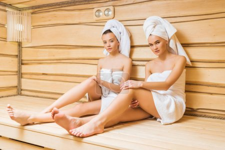 attractive young women relaxing in sauna and looking at camera