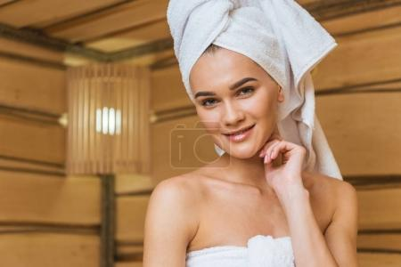 beautiful young woman with towel on head at sauna