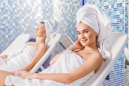 young women relaxing on sunbeds at spa center