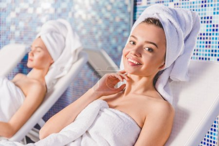happy young women relaxing on sunbeds at spa center