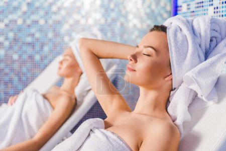 young women covered with towels relaxing on sunbeds at spa center