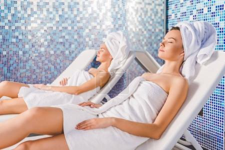 Photo for Attractive young women relaxing on sunbeds at spa center - Royalty Free Image