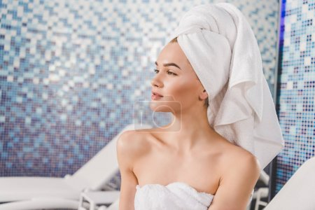 thoughtful attractive woman with towel on head at spa