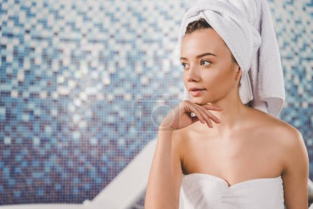 thoughtful young woman with towel on head at spa salon
