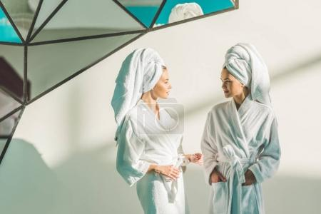 beautiful young women in bathrobes at spa center