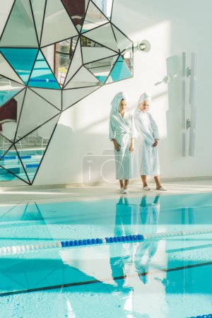 attractive young women in bathrobes standing next to swimming pool at spa center