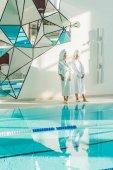 """Постер, картина, фотообои """"привлекательные молодые женщины в халаты, стоя рядом с плавательный бассейн в спа-центре"""""""