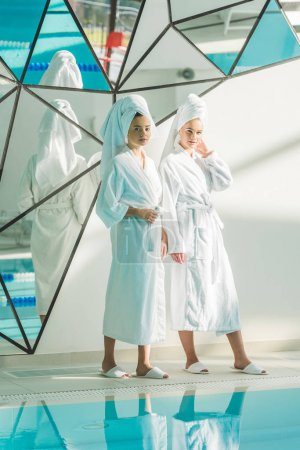 beautiful young women in bathrobes standing next to swimming pool at spa center