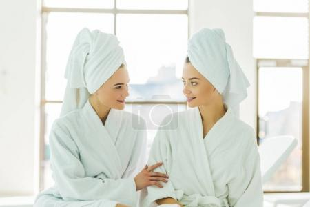 Photo for Beautiful young women in bathrobes and towels on head talking to each other at spa center - Royalty Free Image