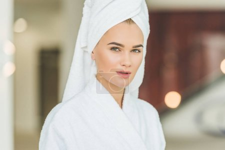 beautiful young woman in bathrobe and towel in spa salon looking at camera