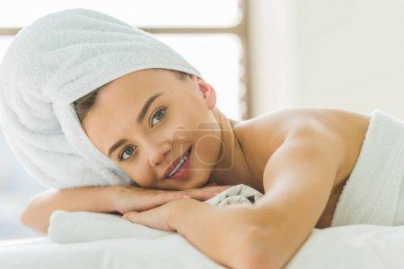 Photo pour Belle jeune femme relaxante sur table de masage au salon de spa - image libre de droit