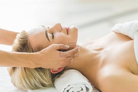 smiling young woman having facial massage at salon