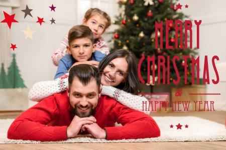 """Photo pour Heureux jeune famille couché ensemble sur le tapis et souriant à la caméra à Noël, avec """"Joyeux Noël et Bonne année"""" lettrage - image libre de droit"""