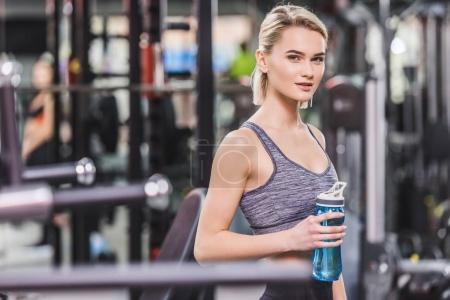 beautiful young woman with water bottle at gym