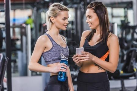beautiful athletic women checking training results on smartphone at gym
