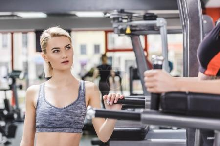 young woman looking at other woman exercising on gym machine