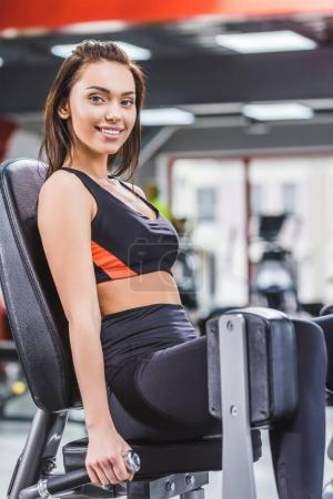 happy young woman exercising on gym machine and looking at camera