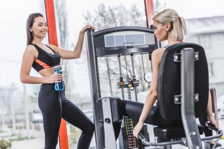young sportive woman working out with gym machine while her partner resting with water bottle next to her at gym