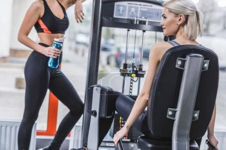 attractive athletic woman working out with gym machine while her partner resting with water bottle next to her at gym