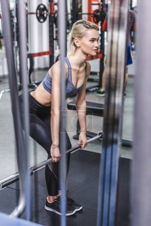 attractive young sportive woman doing deadlift at gym