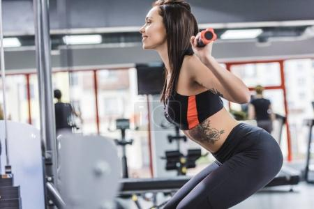 side view of attractive young sportive woman doing squats at gym