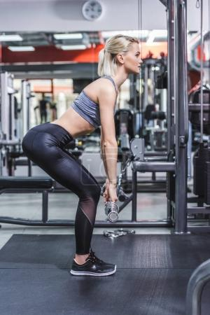 side view of attractive young sportive woman doing deadlift at gym