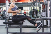 side view of sportive young woman working out with row machine at gym