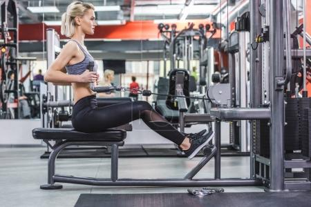 side view of young woman working out with row machine at gym