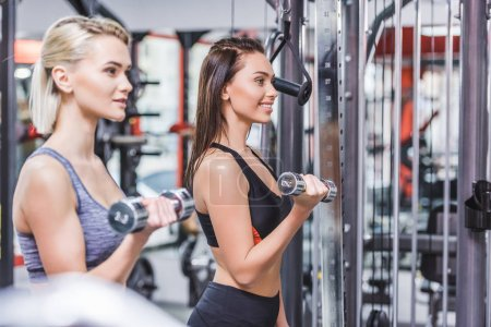 smiling sportive women working out with dumbbells at gym