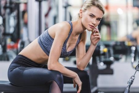 young beautiful woman in modern sportswear relaxing after workout
