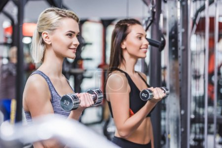 Photo for Attractive athletic women working out with dumbbells at gym - Royalty Free Image
