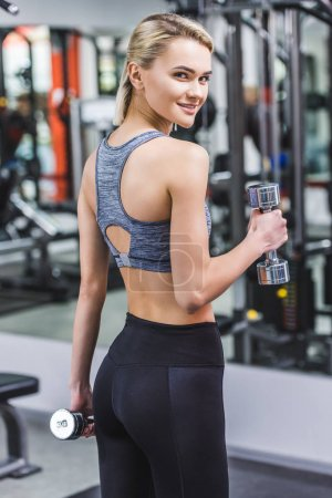Photo for Cropped shot of young woman working out with dumbbells at gym - Royalty Free Image