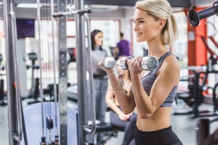 attractive young woman working out with dumbbells at gym