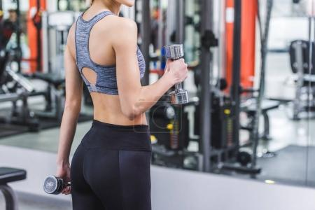 cropped shot of sportive woman working out with dumbbells at gym