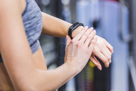 cropped shot of woman checking fitness tracker