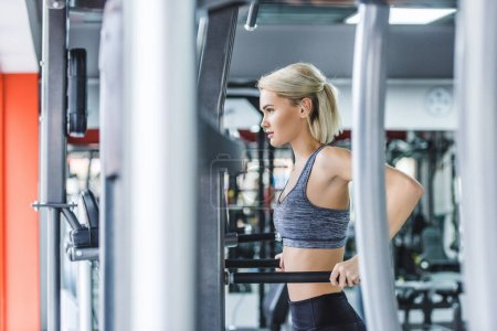 attractive woman in modern sportswear doing exercise on push up bars at gym
