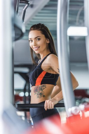 young beautiful woman working out on push up bars at gym